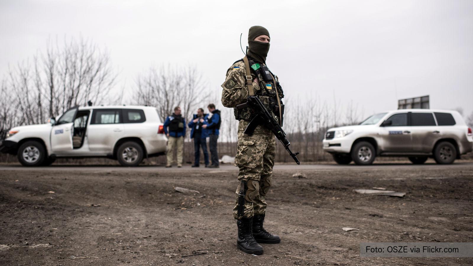 Ukrainischer Soldat vor OSZE-Beobachtern