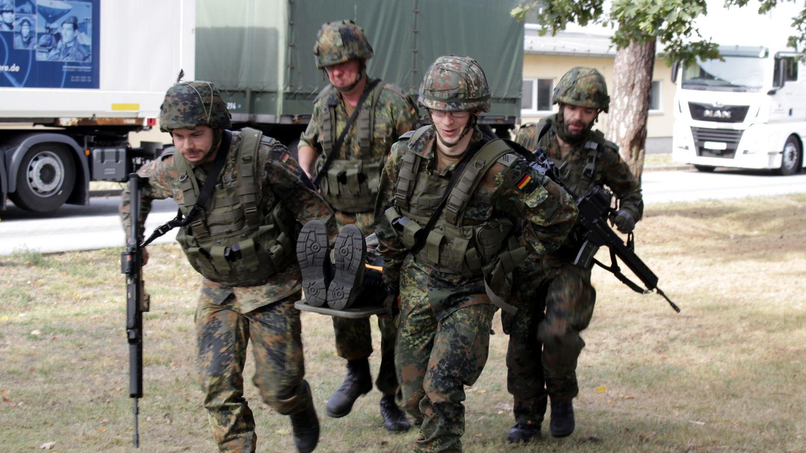 Vier Reservisten tragen eine Person mit einem Bergetuch