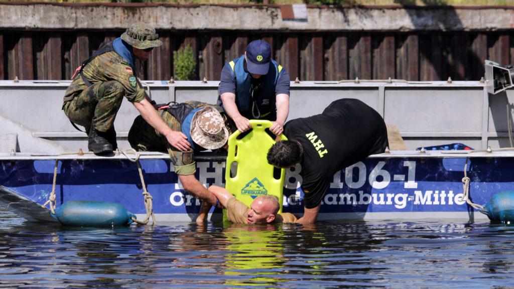 Eine Person in Seenot wird in ein Boot geholt