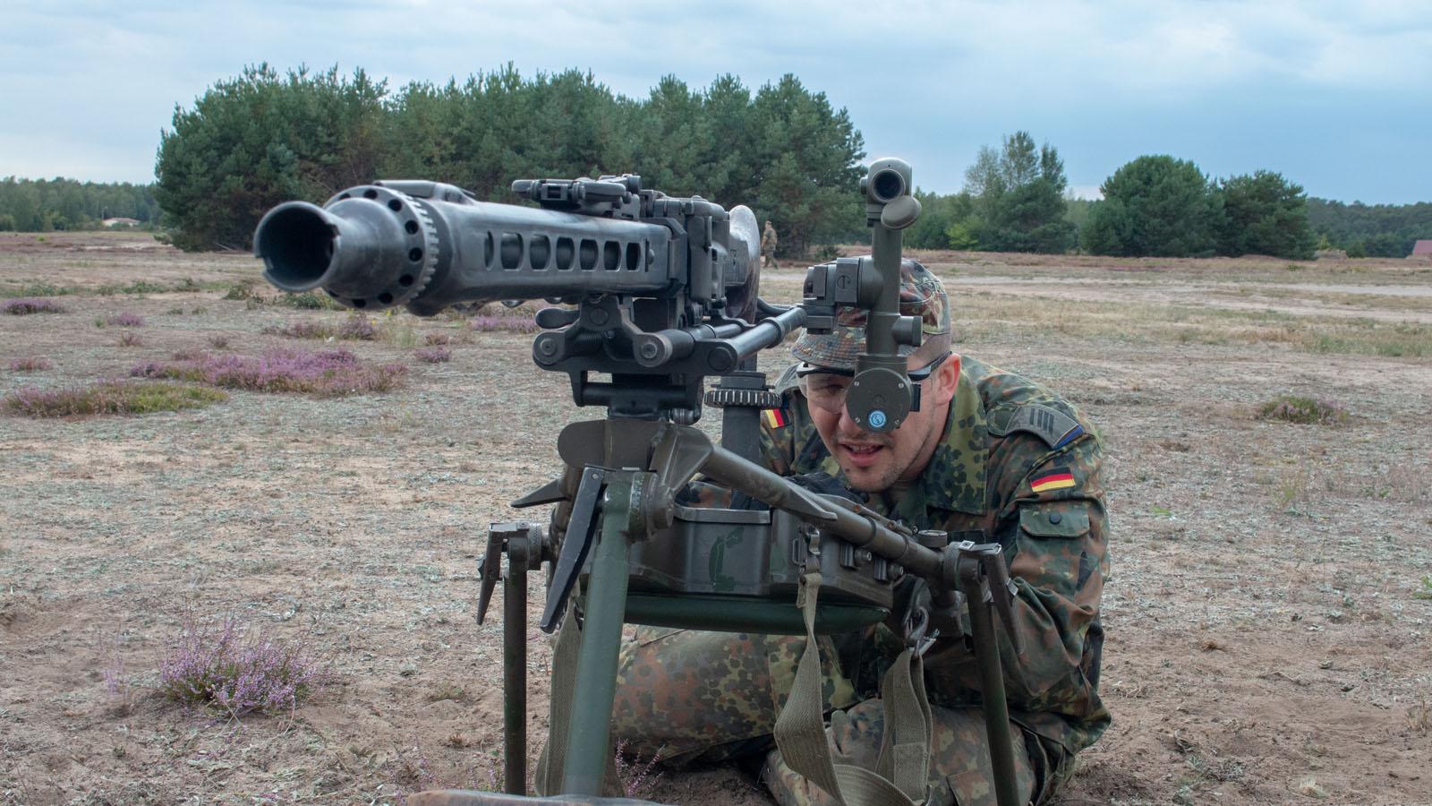 Ein Reservist schaut durch das Zielfernrohr der Erdziellafette